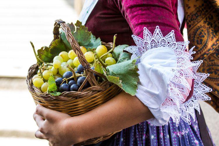 Frau in sardischer Tracht mit Weintrauben